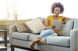 Image of a lady sat on a sofa looking at an electronic tablet device